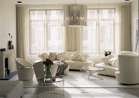 Modern-living-room-with-glass-small-table-white-sofa-carpet-with-armchair-and-drapery-with-fireplace