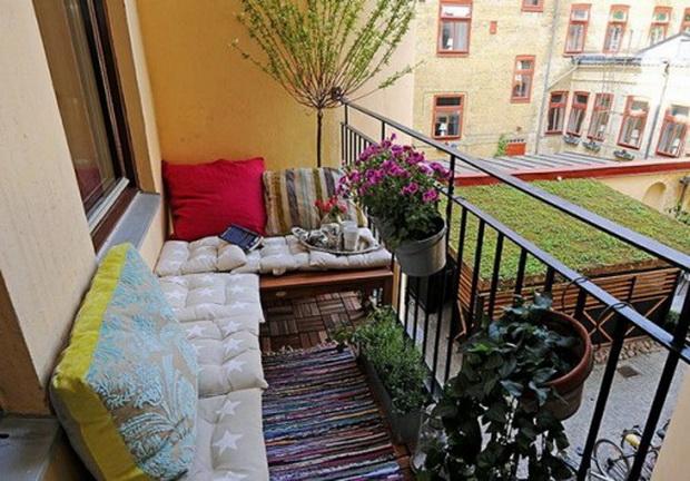 интерьер открытого балкона с подушками и цветами