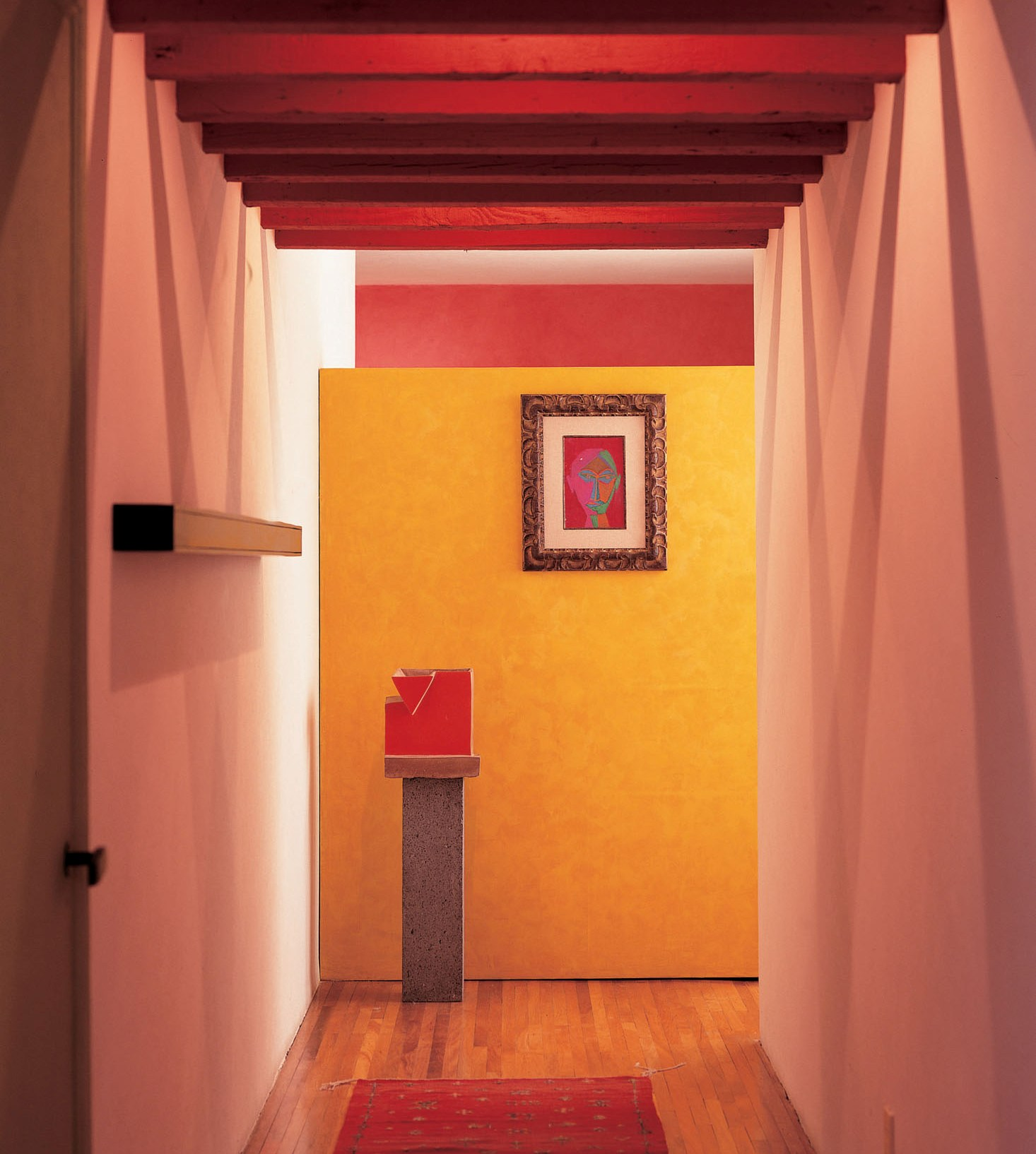 A cheerful Mexican color palette and strategic use of ceiling beams gave better proportion to a long, narrow corridor.