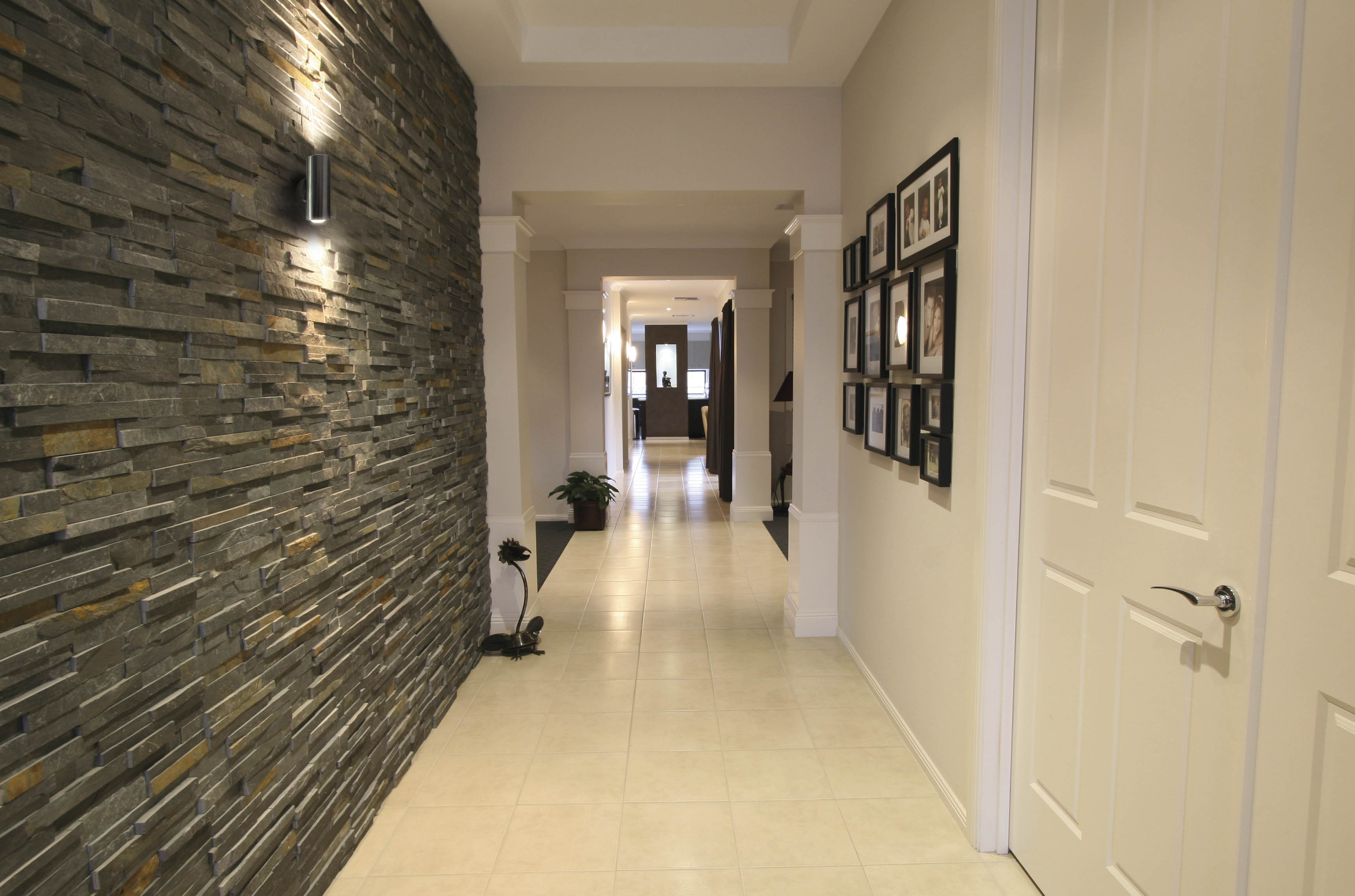 Looking down the hallway of a modern home with whote tiles for flooring and stoneword wall on left.